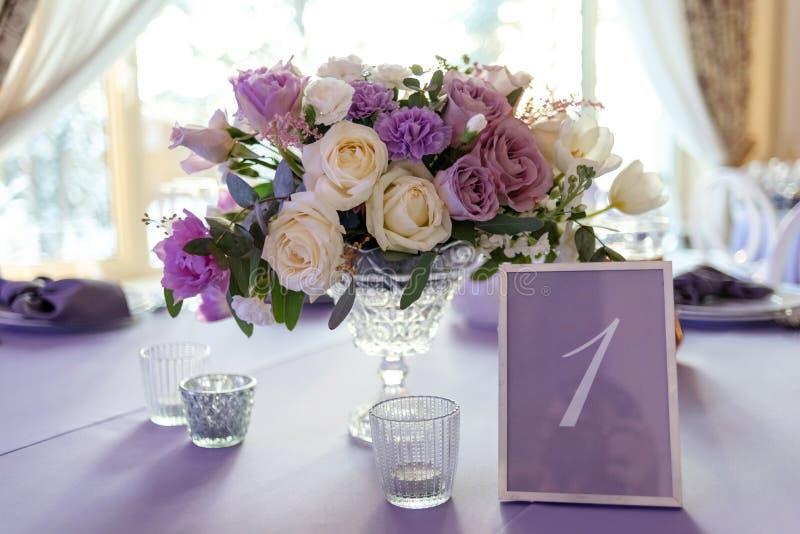 Klassisk garnering av en gifta sig tabell vid låg sammansättning från blommor och ett kort med nummer av en tabell royaltyfria foton