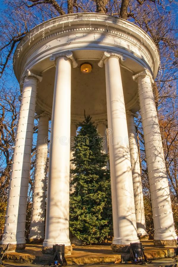 Klassisk gazebo för stor trädgård med julgranen i mitt och mycket blåa ljus som strängas runt om kolonner mot trädfilialer och royaltyfri fotografi