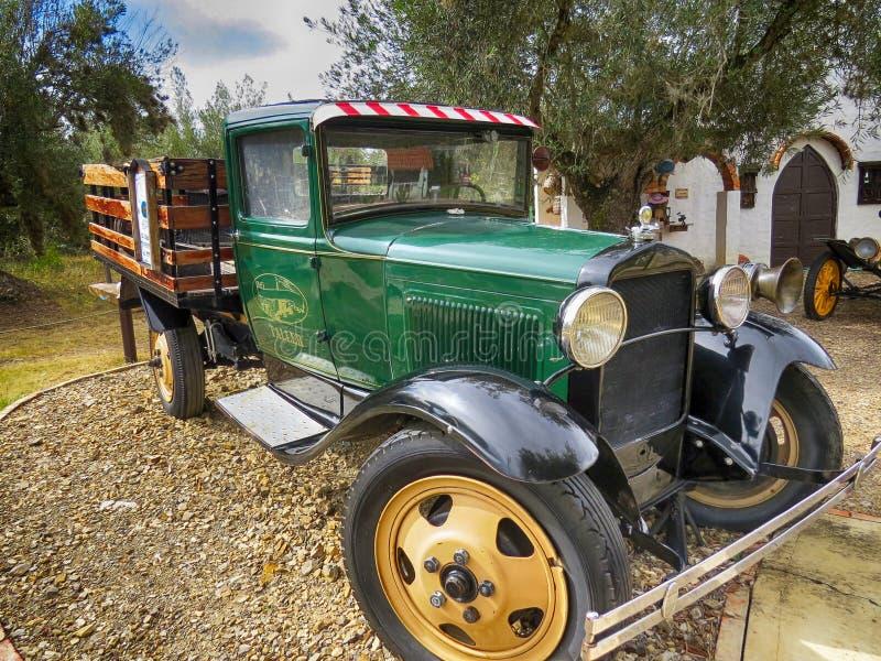 Klassisk grön seminariumskåpbil med träinsatser som parkeras i gammalt kolonialt hus arkivbild