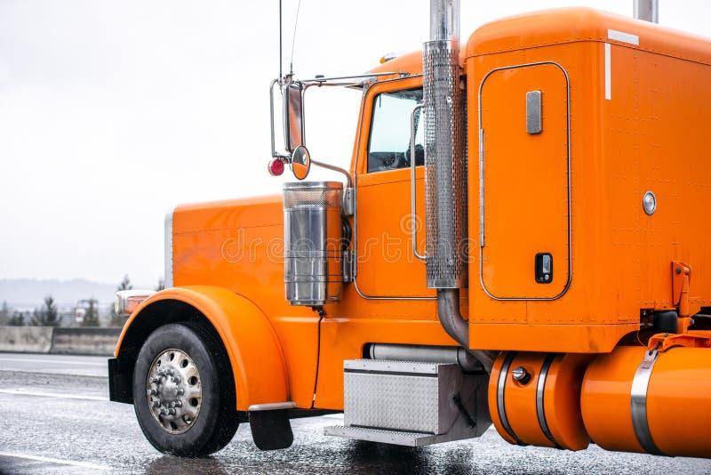 Klassisk halv lastbil för ljus orange stor rigg som kör på den våta vägen, i att regna väder arkivbilder