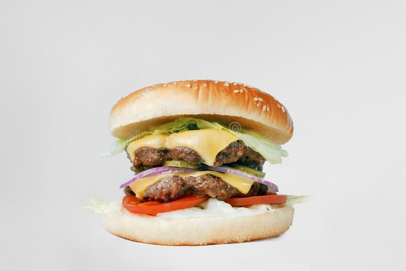 Klassisk hamburgare med en dubbel fläskkotlett och grönsaker på ett ljus - grå bakgrund arkivbild