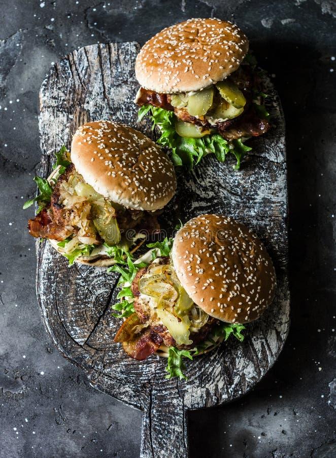 Klassisk hemlagad hamburgare med grisköttkotletten, bacon, knipor, stekte lökar och majonnässenapsås på träskärbräda, på royaltyfri fotografi