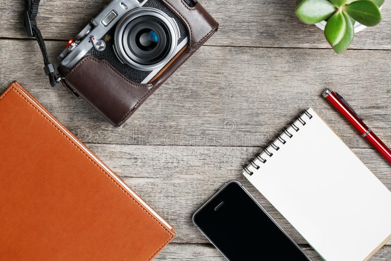 Klassisk kamera med den tomma notepadsidan och röd penna på den gråa trä, tappningtabellen med telefonen och den gröna blomman Br royaltyfri foto