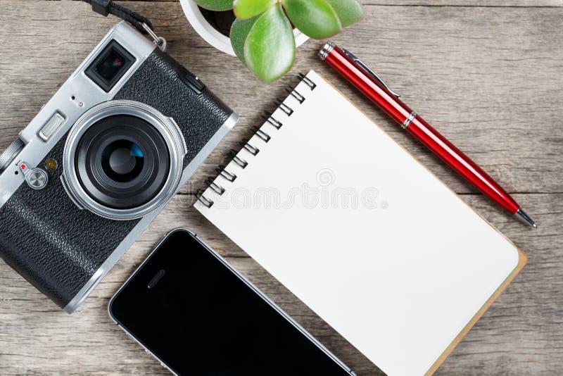 Klassisk kamera med den tomma notepadsidan och röd penna på grått trä, tappningskrivbord med telefonen royaltyfria foton