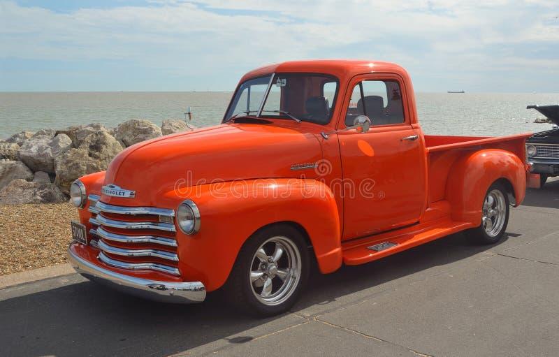 Klassisk ljus orange Chevrolet pickup royaltyfria foton
