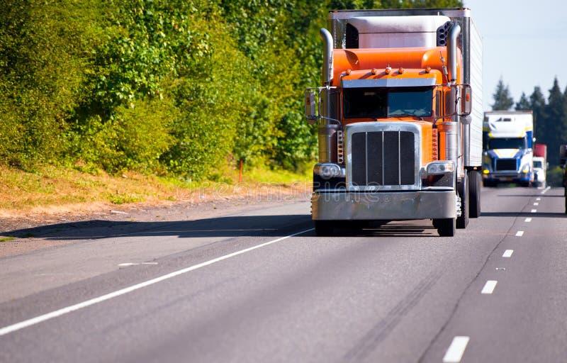 Klassisk orange halv lastbilmarijuanacigarettsläp på hög väg fotografering för bildbyråer