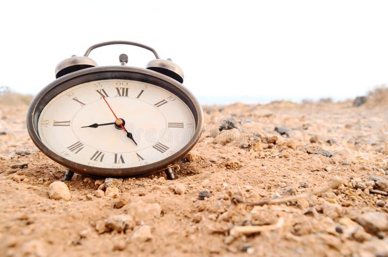 Klassisk parallell klocka i sanden arkivfoto