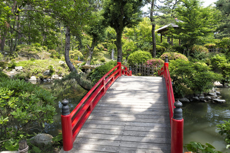 Klassisk röd bro i en japansk trädgård royaltyfria foton