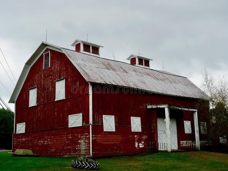 Klassisk röd ladugård med vitt som stigas ombord upp Windows royaltyfri bild
