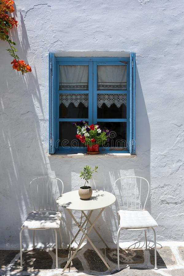 Klassisk sikt av ett grekiskt blått fönster med kaffetabellen och stolar på den Cyclades ön royaltyfri bild
