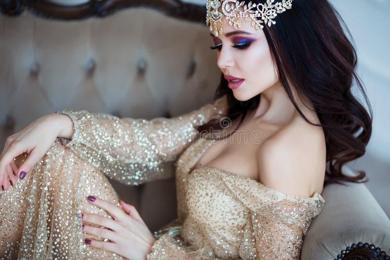 klassisk skönhet Härlig ung kvinna med stilfullt brunetthår och den eleganta klänningen som vilar i lyxig vit klassiker royaltyfria bilder