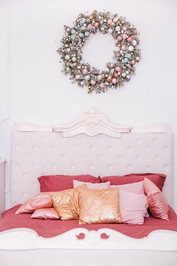 Klassisk sovruminre i nytt års stil Julkrans över sängen royaltyfri bild