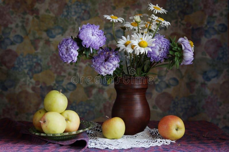 Klassisk stilleben med äpplen och härliga blommor i en vas arkivbild