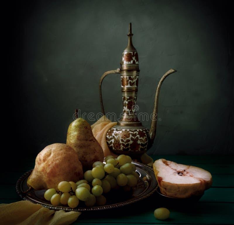 Klassisk stilleben med tillbringaren, päron och druvan på trätabellen royaltyfri fotografi