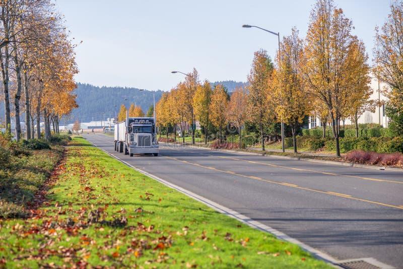 Klassisk svart halv lastbil för stor rigg med halva släpet i stora partier som på flyttar vägen med gula träd för höst royaltyfria foton