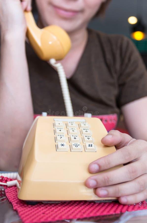 Klassisk tappningtelefon för Closeup med suddighetsflickan som kallar, fokus arkivfoton