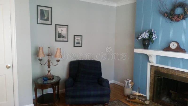 Klassisk vardagsrum med den blå väggen och stol arkivfoto