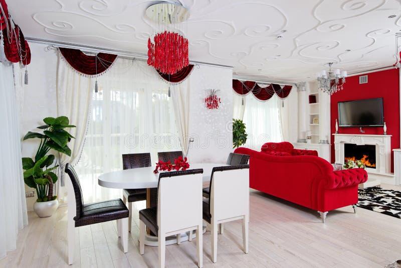Klassisk vardagsruminre i vita och röda färger med dinn arkivfoto