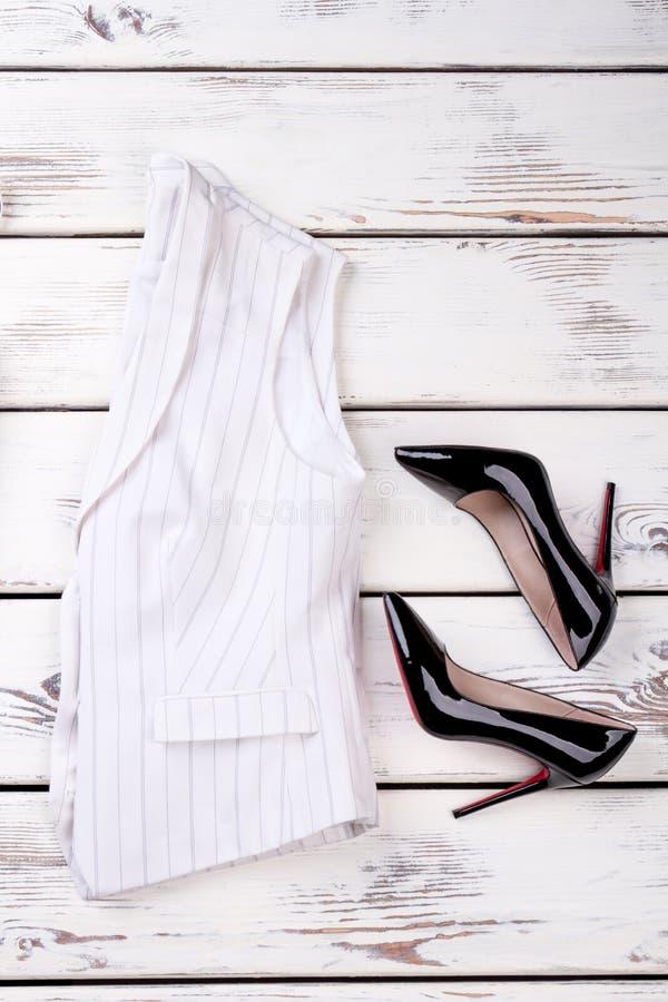 Klassisk waistcoat för kvinnor och svarta stiletter arkivfoton