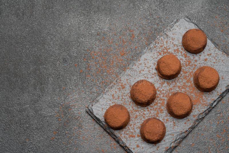 Klassiska chokladtryfflar p? m?rk konkret bakgrund arkivfoto