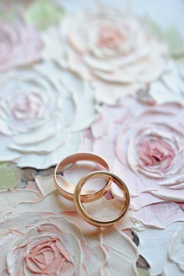 Klassiska guldbröllopcirklar på den blom- målade rosbakgrunden 1 kortinbjudan arkivfoton