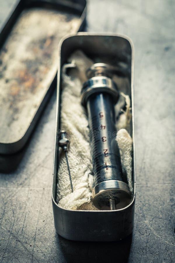 Klassiska injektionssprutor med en visare i en rostfritt stålbehållare arkivbilder
