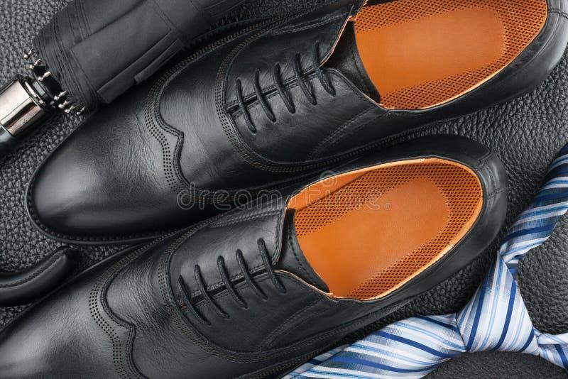Klassiska mäns skor, band, paraply på det svarta lädret arkivbilder