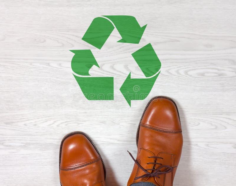 Klassiska mäns skor med ett återvinningsymbol på golvet arkivfoto