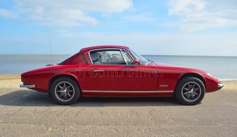 Klassiska röda Lotus Elan +2 motorisk bil som parkeras på sjösidapromenad arkivfoto