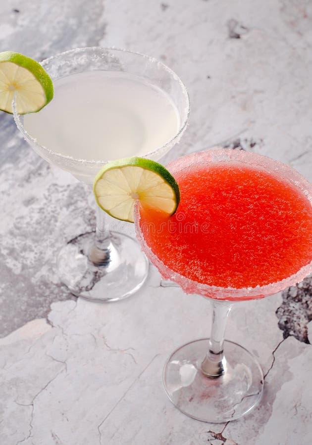 Klassiska två och coctail för margarita för jordgubbe vit och röd alkoholiserad, med garnering av salt på kanten av exponeringsgl fotografering för bildbyråer