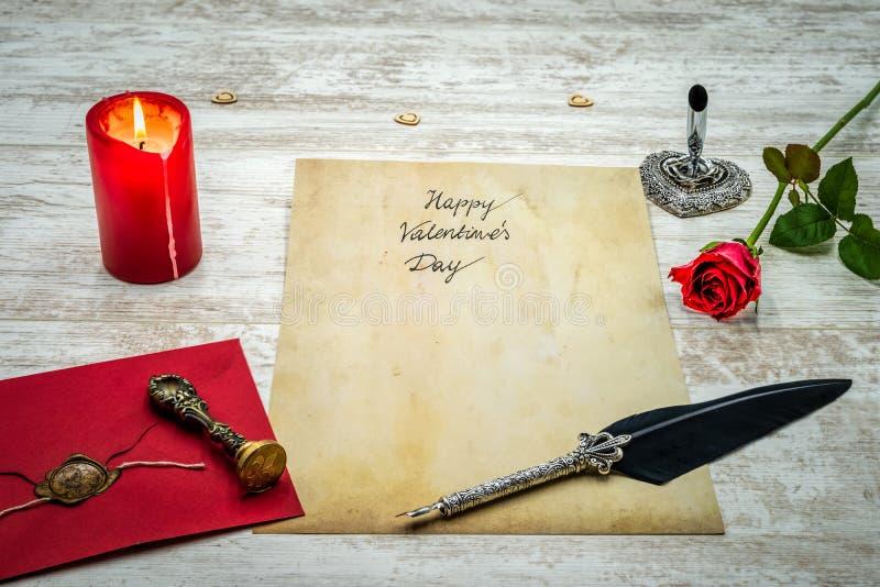 Klassiska valentins dag CAD med den dekorativa vingpennan och ställningen som är röda packar in med vaxskyddsremsan, röd stearinl royaltyfri foto