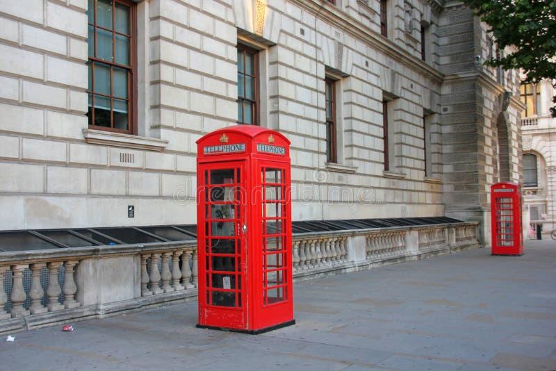 Klassiskt brittiskt rött telefonbås på den gamla gatan av London, UK arkivfoto