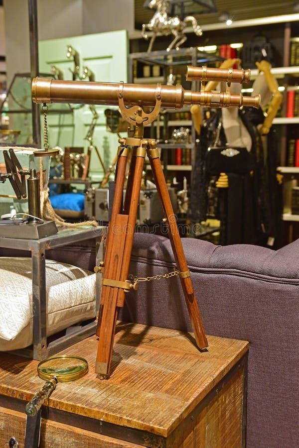 Klassiskt designteleskop med träbenservice i en shoppa som säljer tappninggods arkivbilder