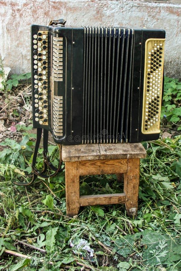 Klassiskt musikinstrumentdragspel för gammal tappning på en sjaskig trästol i borggården av ett byhus mot en vit vägg arkivbild