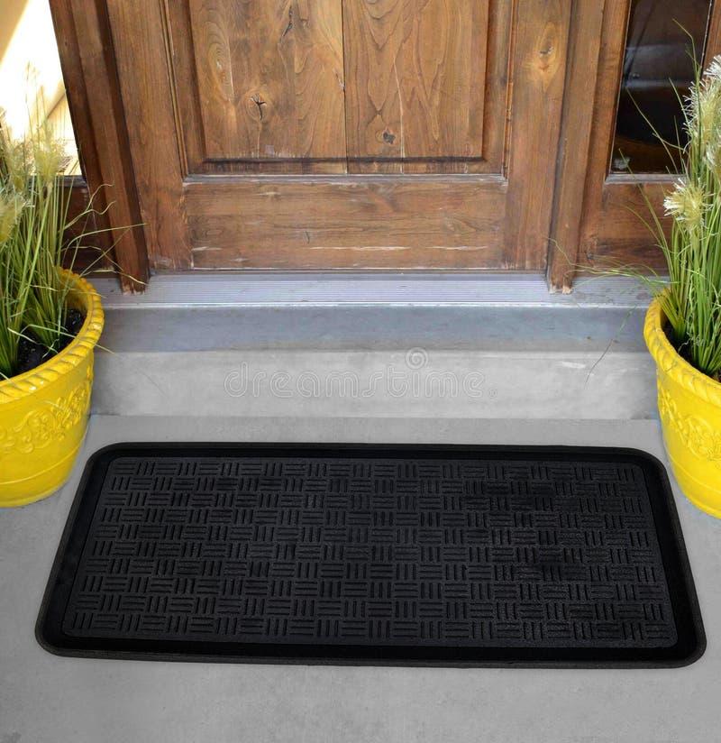Klassiskt svart texturerat rundat mattt för hörnrektangeldörr med gula blommor och sidor fotografering för bildbyråer