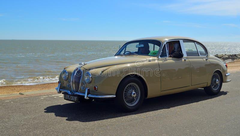 Klassiskt tänd - bruna Jaguar motoriska bilen som den är drivande längs sjösidapromenad arkivbilder