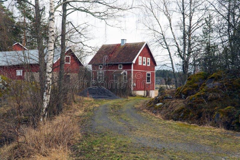 Klassiskt traditionellt rött trähus i Skandinavien bygd, Finland royaltyfri fotografi