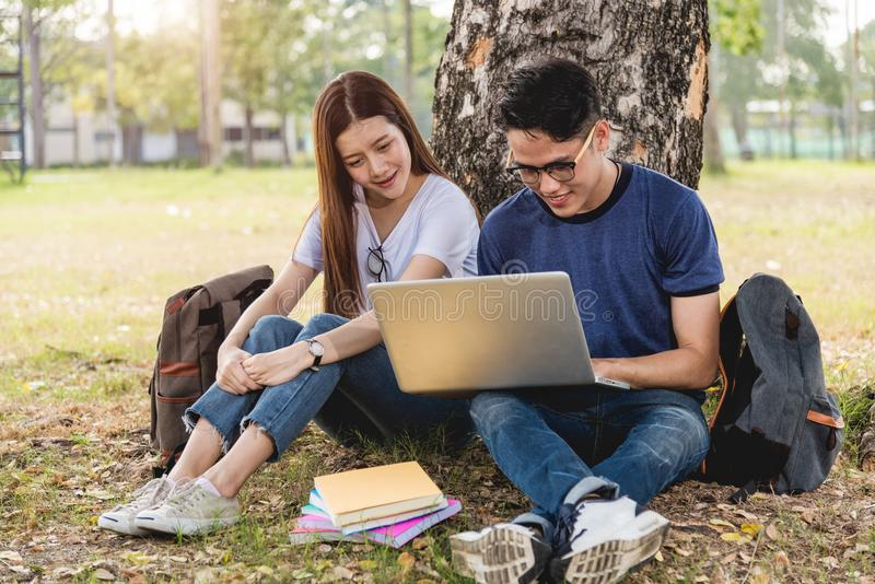 Klasskompisar för den unga mannen som och för flickavännen sitter under träd, konsulterar royaltyfria foton