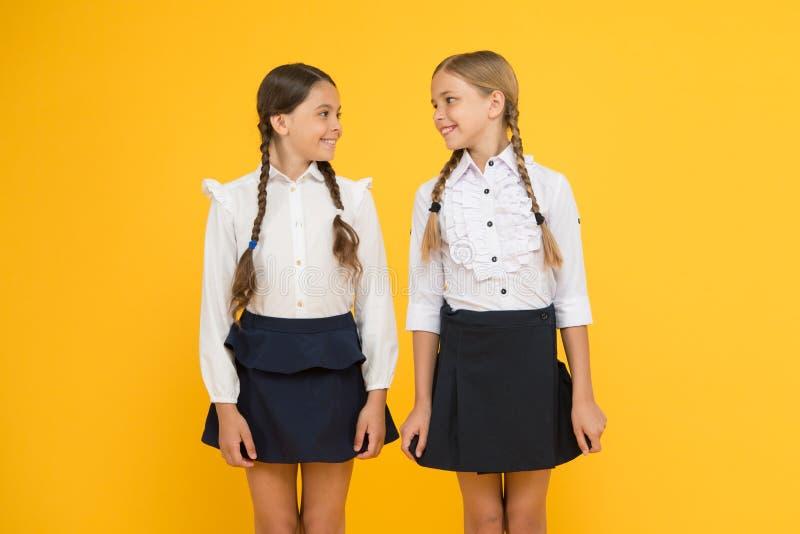 Klasskompisar som har gyckel på skola Förtjusande elever för vänner För stilskola för skolflickor formell likformig lycklig barnd arkivfoto