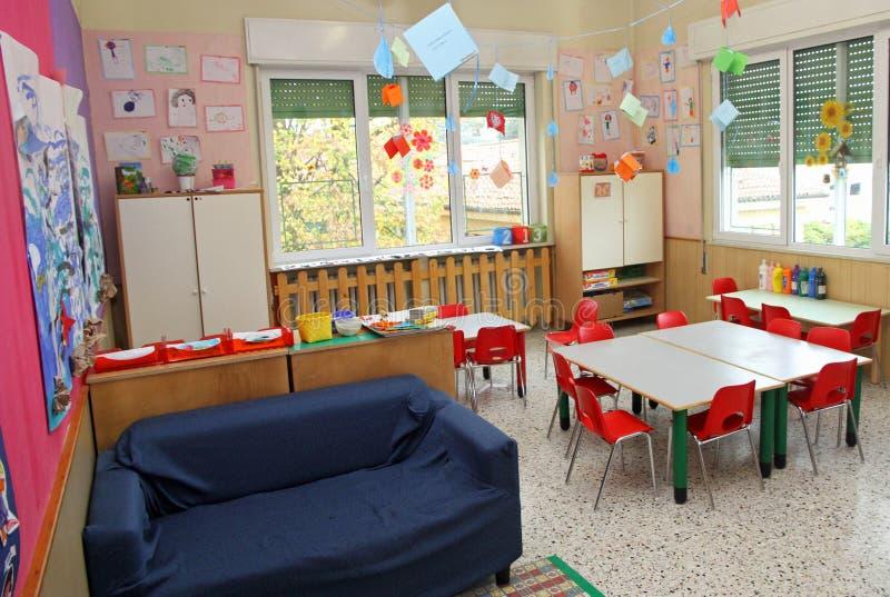 Klassrum i ett dagis med tabeller och stolar och blå soffa royaltyfri foto