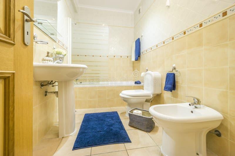 Klasyczna łazienka z błękitnym dywanikiem i ręcznikami obrazy royalty free