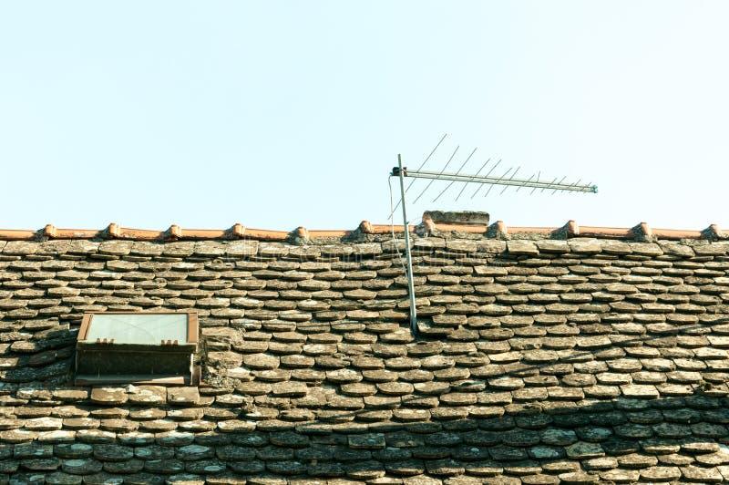 Klasycznego rocznika analogowa telewizyjna antena na starym domu dachu z płytkami i okno obrazy stock