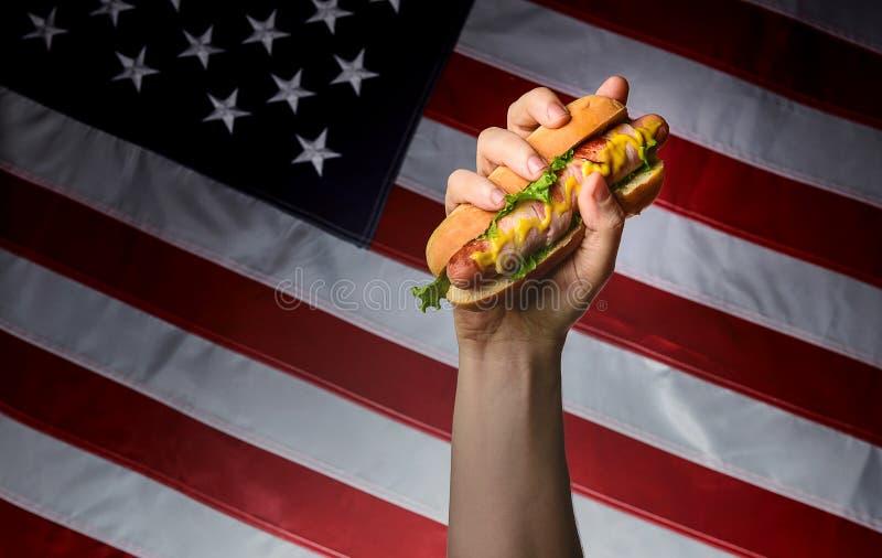 Klasyczny amerykański hot dog w ręce na flaga amerykańskiej tle zdjęcie stock