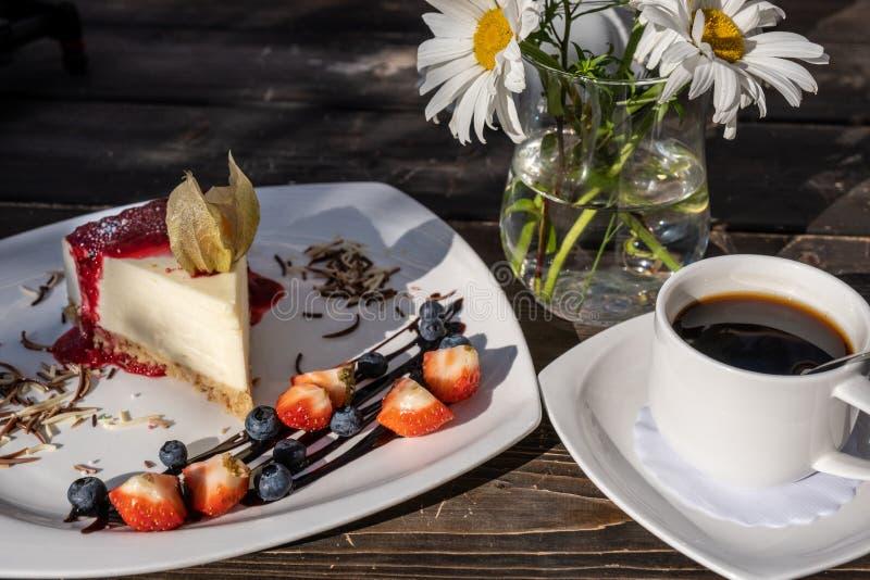 Klasyczny cheesecake z malinowym dżemem na talerzu dekorował z świeżymi truskawkami i filiżanka kawy zdjęcia royalty free