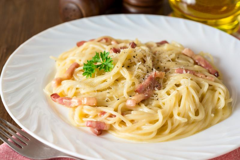Klasyczny makaronu carbonara Spaghetti z bekonem, jajecznym yolk i parmesan serem na bielu talerzu na ciemnym drewnianym tle, zdjęcie stock