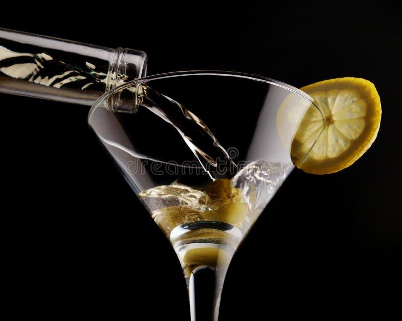 Klasyczny Martini w zazębionym szkle nad czarnym tłem, garnirującym z oliwką i cytryną fotografia royalty free