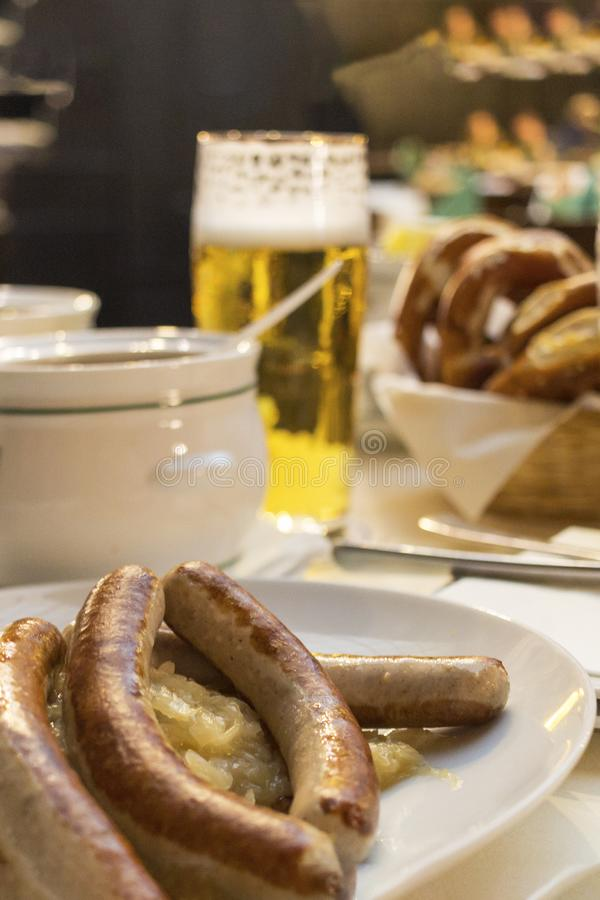 Klasyczny Niemiecki go?? restauracji sma?y? kie?basy z braised kapust? na wielkich biel talerzach z lekkim piwem, stoi na stole w zdjęcia stock
