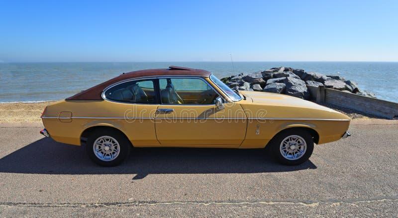 Klasyczny złoto 2 (0) litrów Ford Capri Ghia Motorowy samochód Parkujący na nadbrzeże deptaku fotografia stock