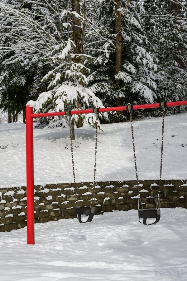Klasyk huśtawka ustawiająca w jawnym parku, czerwonego poparcia gumowych dziecko huśtawki siedzeniach, statywowych i czarnych, śn zdjęcie royalty free
