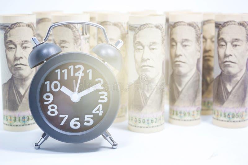 Klasyka zegar Na rolce banknot, pojęcie I pomysł czas jenu, zdjęcie royalty free